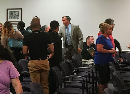 Waynesboro City Manager Mike Hamp (center) meets with residents after a city council meeting on Monday. Nine people spoke, and many more showed up, demanding the city take more action against hate groups.