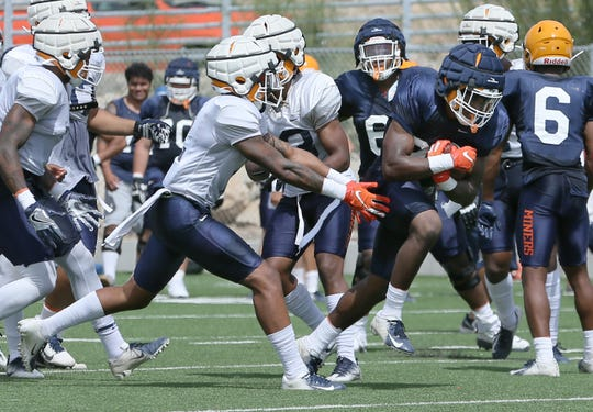 UTEP senior defesive back Michael Lewis stops running back Ronald Awatt during their practice Tuesday at Glory Road Field.