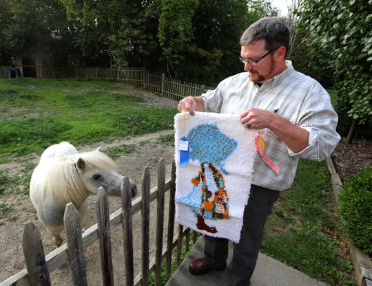 Dennis Rush and his horse, Fang, and a hook art piece by his daughter, Ginger, at his Staatsburg home Aug. 12, 2019.