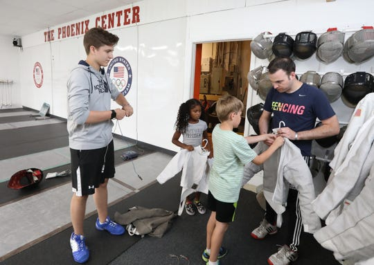 Mason Moskowitz of Poughkeepsie, left, works with students at the Phoenix Fencing Center summer camp in Poughkeepsie  Aug. 13, 2019. He recently won three medals in fencing at the Maccabi Games in Hungary.