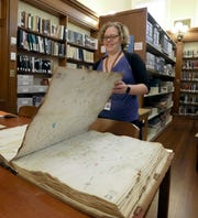 Kira Thompson, local history librarian, turns the pages of a Sanborn fire insurance map book at the Adriance Memorial Library in Poughkeepsie Aug. 13, 2019.