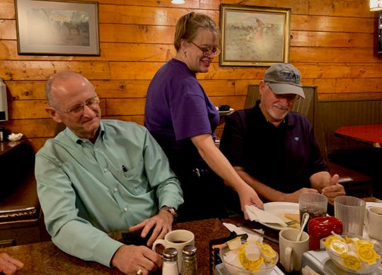 Christy Clark, who worked for Pioneer of Texas on Maplewood before becoming a first-year teacher, serves Tom Sheriff and Jerry Morgan breakfast. The two are part of a group of men who gather for breakfast once a week and have cheered Clark on as she reached for her dream of teaching.