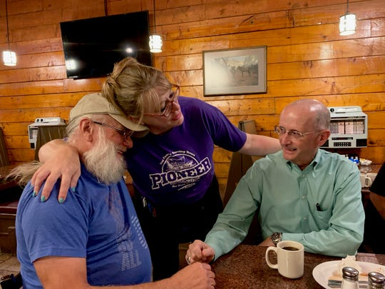 Christy Clark, who will begin her dream job as a first-year teacher Thursday, embraces one of her biggest cheerleaders, customer Larry Ferguson. Ferguson and Tom Sheriff, right, are part of a group of men who meet once a week at Pioneer of Texas on Maplewood.