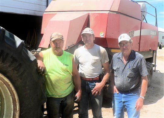 Daryl, left, and Clayton, center, rent the farm from their dad, Cliff Hageman.