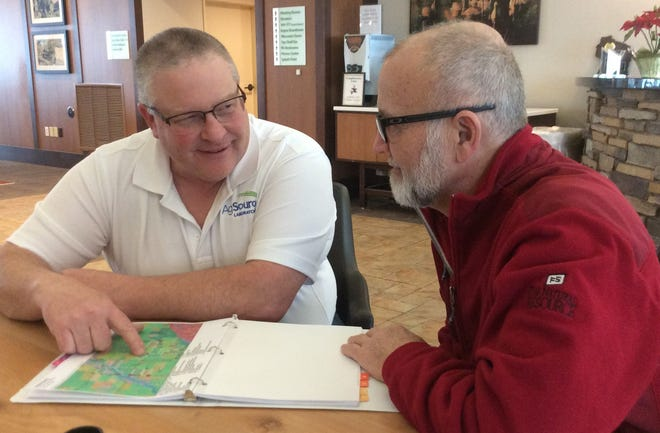 AgSource NMP/GPS Manager, Chuck Bolte, left, consulting a farmer on plan.