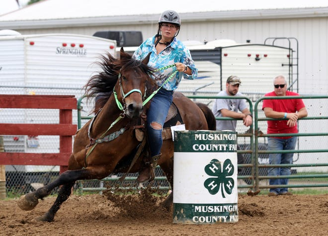 A contestant runs in the barrel race at the Muskingum County Fair on Tuesday morning.