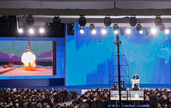 Russian President Vladimir Putin delivers his annual address to the Federal Assembly while a screen shows a newly developed cruise missile with 'no range limitation' at the Manezh Central Exhibition Hall in Moscow.