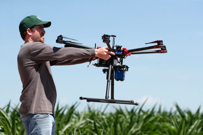 In this Thursday, July 11, 2019, photograph, United States Department of Agriculture intern Alex Olsen prepares to place down a drone at a research farm northeast of Greeley, Colo.