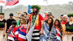 Actor Jason Momoa holds the hands of his children, Nakoa-Wolf Momoa, left, and Lola Momoa, right, as he is welcomed with a hula while visiting elders and Native Hawaiian protesters blocking the construction of a giant telescope on Hawaii's tallest mountain, at Mauna Kea Access Road on July 31, 2019, in Mauna Kea, Hawaii.