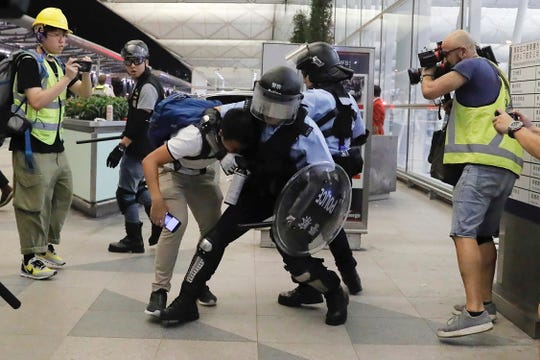 Policemen in riot gears arrest a protester during a demonstration at the Airport in Hong Kong, Tuesday, Aug. 13, 2019.