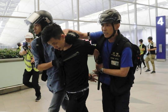 Policemen arrest a protester during a demonstration at the Airport in Hong Kong, Tuesday, Aug. 13, 2019.