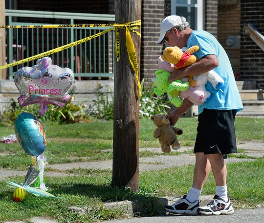 Paul Laughlin, 57, places stuffed animals on Sunday, Aug. 11, 2019 outside a home at 1248 West 11th St. in Erie, Pa., where multiple people died in an early-morning fire.   (Greg Wohlford/Erie Times-News via AP) ORG XMIT: PAERI102