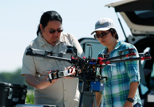 In this Thursday, July 11, 2019, photograph, United States Department of Agriculture engineering technician Kevin Yemoto, left, loads a camera into a drone as Huihui Zhang looks on at a research farm northeast of Greeley, Colo.