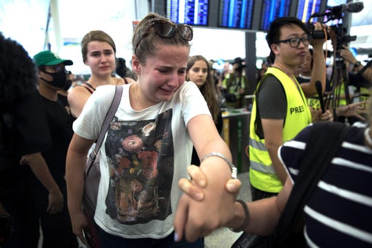 Travelers react as they manage to walk through the protesters to the departure gates during a demonstration at the Hong Kong International Airport in Hong Kong, Tuesday, Aug. 13, 2019.
