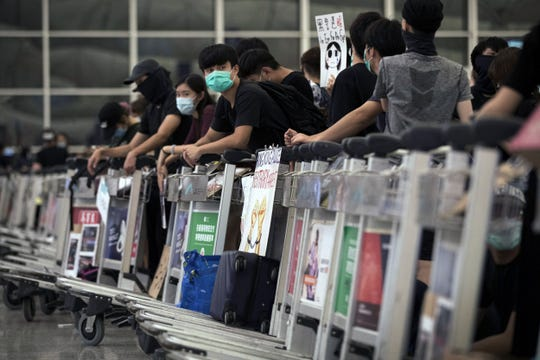 Protesters use luggage trolleys to block the departure gates during a demonstration at the Airport in Hong Kong, Tuesday, Aug. 13, 2019.