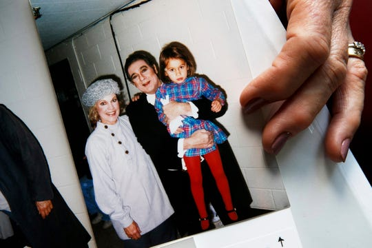 "At her home in rural northern Virginia, opera singer Patricia Wulf holds a 1998 photo of herself with opera star Placido Domingo holding her 4-year old daughter after a performance of ""Fedora"" at the Washington Opera. In interviews, Wulf said Domingo repeatedly propositioned her as she walked off stage, often knocked on her dressing room door asking to come in and that she tried to dodge his advances by hiding from him."