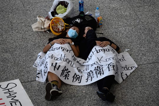 Protesters rest on the floor of Hong Kong's international airport on August 13, 2019, the day after the airport closed due to pro-democracy protests.