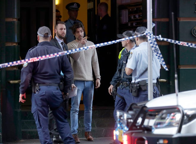 A man, center, points as he assists police at a building where a person has been found deceased after a man attempted to stab multiple people in Sydney, Australia, Tuesday, Aug. 13, 2019.
