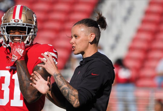 San Francisco 49ers offensive assistant Katie Sowers speaks with running back Raheem Mostert (31) before the game against the Dallas Cowboys at LeviÕs Stadium.