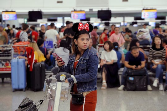 A woman wearing Minnie Mouse headgear looks on as stranded travelers gather near the closed check-in counters at the Airport in Hong Kong, Tuesday, Aug. 13, 2019.