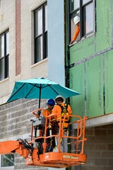 Construction workers keep out of the sun with an umbrella on their boom lift as they work on an apartment building along South Jefferson Davis Parkway in New Orleans on Aug. 13.