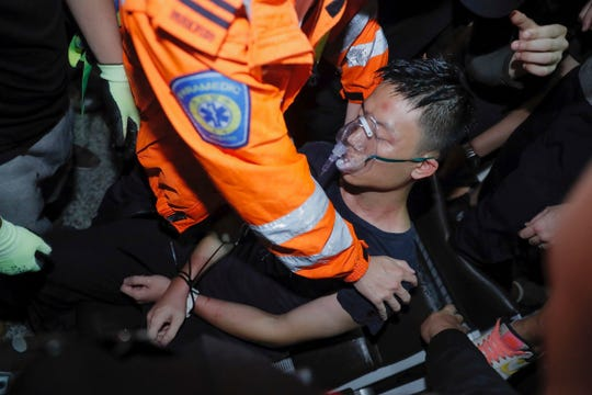 A medical staffer helps a detained man, who protesters claimed was a police officer from mainland China, during a demonstration at the Airport in Hong Kong, Tuesday, Aug. 13, 2019.