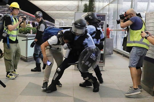 Policemen in riot gears arrest a protester during a demonstration at the Airport in Hong Kong, Tuesday, Aug. 13, 2019. (AP Photo/Kin Cheung)