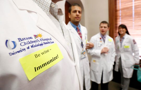 Pediatric residents from the Batson Children's Hospital at the University of Mississippi Medical Center wear stickers calling for the lawmakers to support immunizations during a visit to the Capitol on Feb. 10, 2015, in Jackson, Miss.