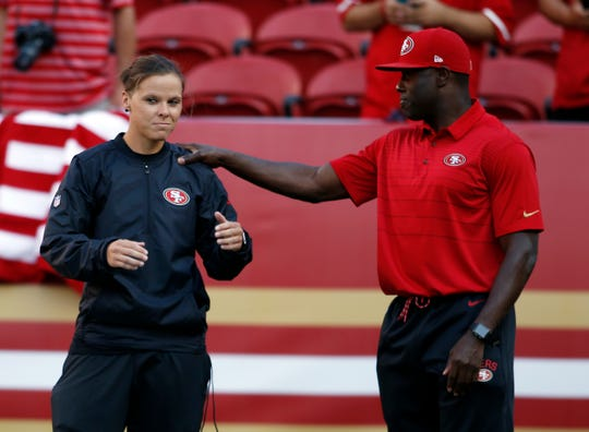 San Francisco 49ers assistant coach Katie Sowers, left, talks with a fellow coach before a preseason NFL football game against the Denver Broncos Saturday, Aug. 19, 2017, in Santa Clara, Calif.
