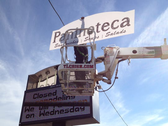 Archive: A worker installed the new Paninoteca sign on the former Sunrise Family Restaurant in Appleton in 2012.