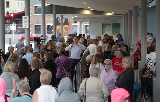 """A crowd of people wait in line outside the Fox Cities Performing Arts Center in August during the initial release of tickets for """"Hamilton."""""""
