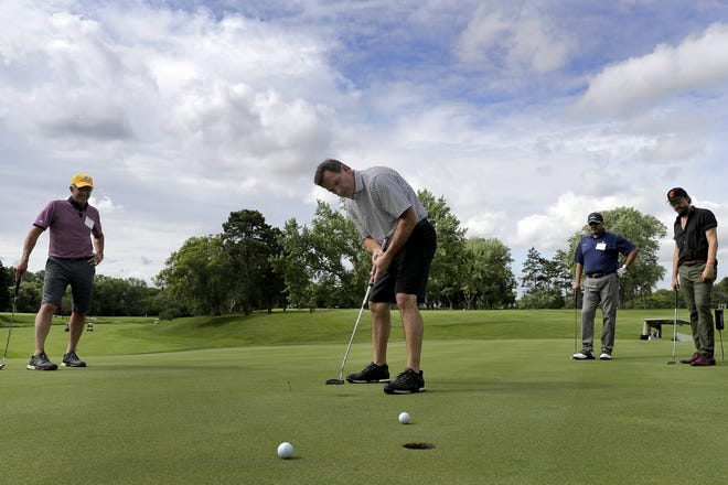 John Schmidt, left, Dr. Imran Andrabi, center right, and Cory Chisel watch as Wilson Jones putts on the first hole during the U.S. Venture Open golf event Wednesday at Butte des Morts Country Club.