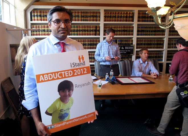 Manalapan's Ravi Parmar holds a poster showing his son Reyansh after a news conference in Red Bank Thursday, August 8, 2019. His son Reyansh was taken by his mother to India.