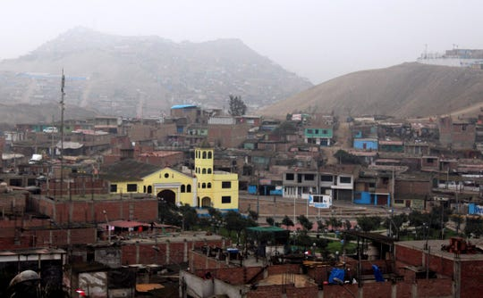 A yellow Catholic church stands out in a hilly neighborhood in Callao, Peru. Homes stretch up the hills and into the mist of a foggy day.
