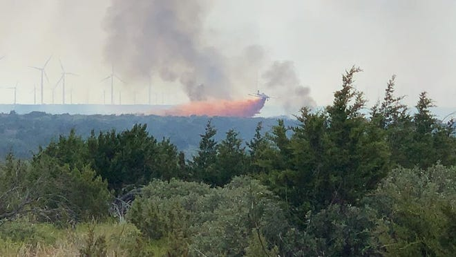 A Texas A&M Forest Service airplane drops fire retardant on the Old Bridge Fire on the 69 Ranch near Maryneal, south of Sweetwater, on Tuesday.