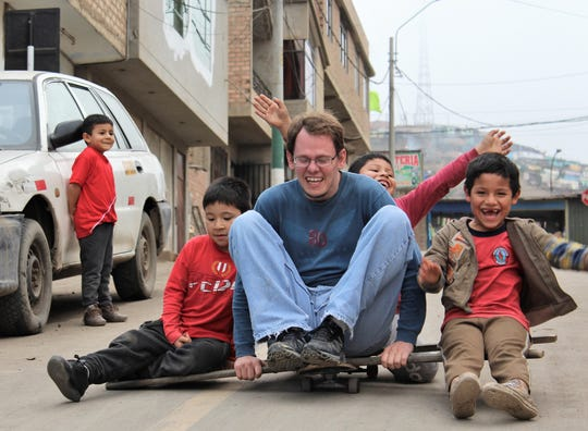 "Texas visitor Keith O'Shields was given the honor of ""driving"" a makeshift rig - a wooden ladder balances across a skateboard - down a hilly street in the Ventanilla district of Callao, Peru. He seems more apprehensive than his young passengers."