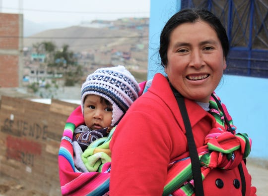 A woman and her child, both colorfully dressed, make their way up a street in Callao, Peru, past a church where an Abilene group spent parts of three days.