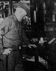 Sgt. James Skeily, of the state police, examines the bullet hole in the bank.