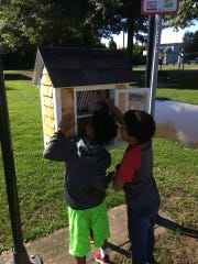 Two boys select books from a Little Free Library at Boland Park on the East Side of Binghamton.
