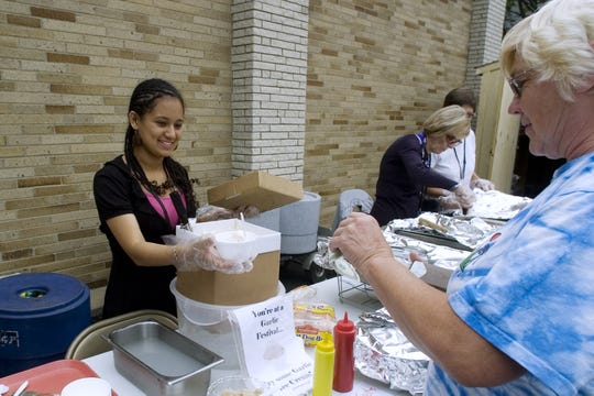 Dawn Pennay of Binghamton purchases a cup of garlic ice cream from festival volunteer Ana Castro on Saturday afternoon during the 2010 Garlic Festival. Satisfied with the unordinary flavor, Pennay was pleased with her purchase.