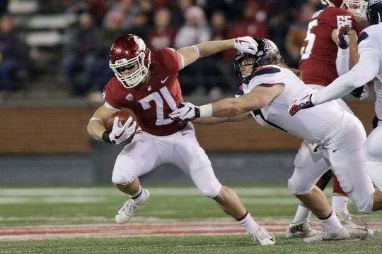 "FILE - In this Nov. 17, 2018, file photo, Washington State running back Max Borghi (21) runs while under pressure from Arizona linebacker Colin Schooler during the first half of an NCAA college football game in Pullman, Wash. The departure of James ""Boobie"" Williams should mean more exposure for Borghi, who earned a starting job last year as a freshman and is expected to be the primary option in the backfield."