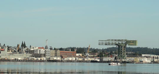 The Admiral Pete cruises past Puget Sound Naval Shipyard as seen from Port Orchard in August. The shipyard has hired thousands to fill new roles and replace retiring workers, and it's put a crimp on businesses trying to tap the same labor pool.