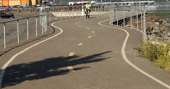 A cyclist pedals down the Bay Street Pedestrian Path behind Westbay Center in Port Orchard on Wednesday. Plans to extend the path to the Annapolis ferry dock are drawing opposition from property owners whose land would be affected.