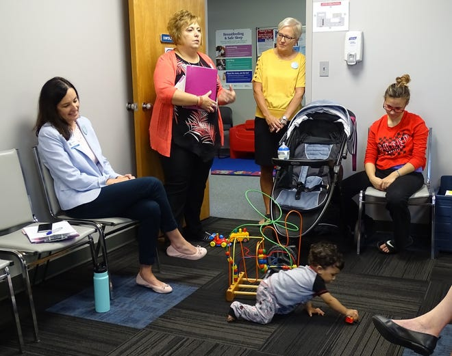 From left, Jennifer Foster of OhioHealth Mothers' Milk Bank, health commissioner Kate Siefert, Kathy Bushey, WIC director, speak as new mom Asia McClellan watches her older son, Nah'mier Fields, 1, play during the opening of a mothers' milk drop-off site at Crawford County Public Health's WIC office on Wednesday.