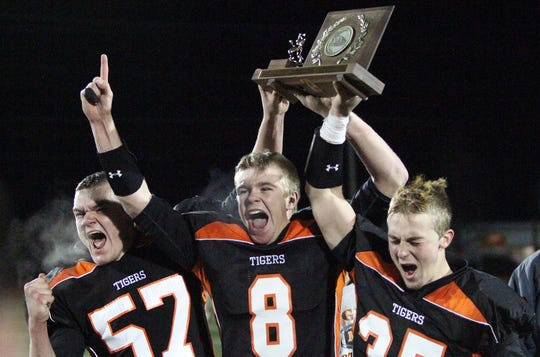 Middlebury's Samuel Usilton, left, Nicholas Felki, center, and Samuel Smith, right, celebrate with the championship trophy after the Tigers defeated South Burlington in the Division I high school football state title game in 2013.