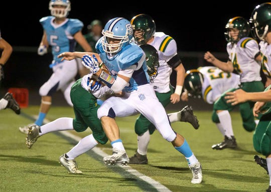 South Burlington's Tanner Contois evades BFA defenders on his way to scoring a touchdown in South Burlington on Friday, September 20, 2013.