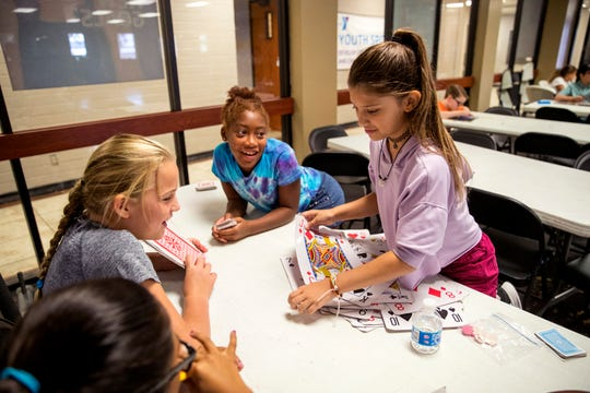 Tianna Reynolds, clockwise from top left, 9, Zylah Gareve, 9, Abigail Jameson, 10, and Kaia Shipley, 9, play a card game while participating in the YMCA summer camp on Wednesday, August 14, 2019. The summer camp is popular because it is a rare summer camp that stays open until just before school starts.