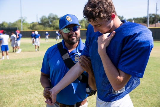 """Odem athletic trainer CJ """"Doc"""" DeLaGarza checks a players arm during practice on Tuesday, Aug. 13, 2019."""