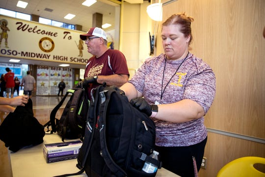 Tuloso-Midway High School athletic director Wade Miller, left, and teacher Mandy Price check student backpacks on Wednesday, August 14, 2019, following a threat of a school shooting that was made the night before online. In addition to a law enforcement presence, students were entering the school at one entrance, were having their backpacks checked and had auxiliary personal stationed around the school as extra eyes.