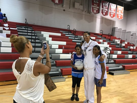 Yohairas De La Rosa takes a photo of her daughters, Yomeidy (left) and Diomeiry, with Camden native and Women's Basketball Hall of Famer Valerie Still.